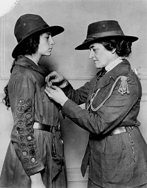 Juliette Gordon Low putting a badge on a girl scout.
